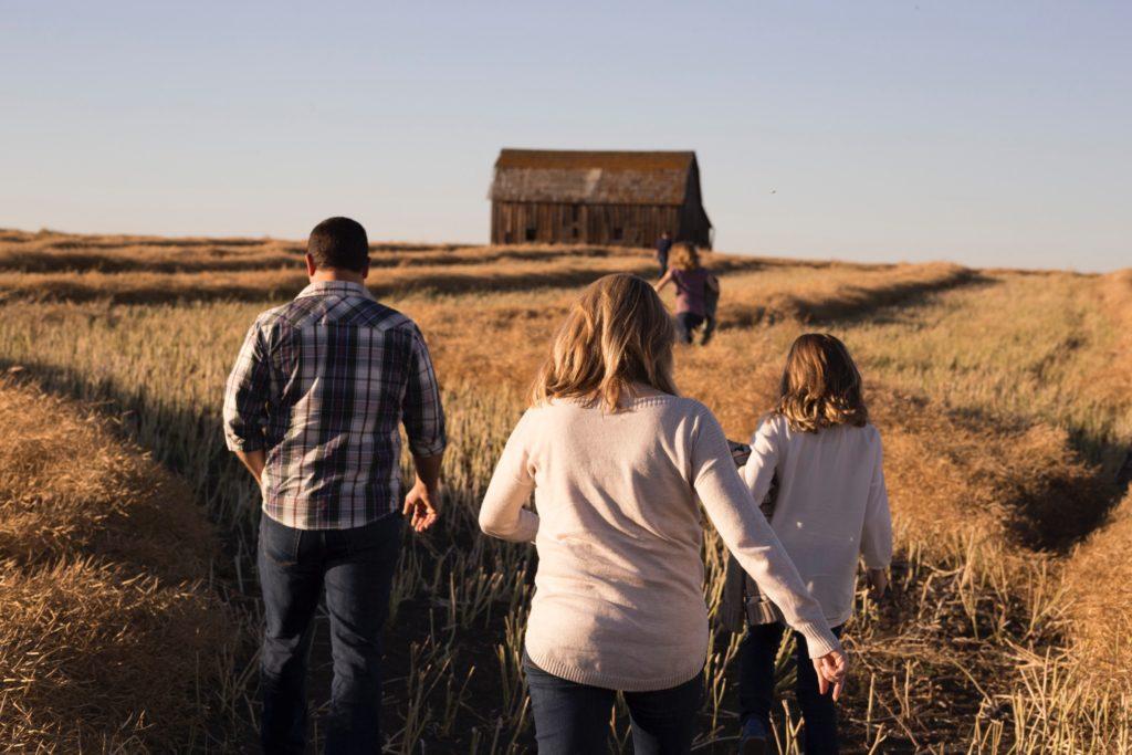 Familia de espaldas andando por un campo