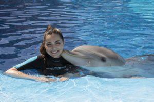 Chica en el agua con un delfín dándole un beso