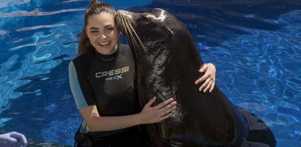 Chica posando con un león marino