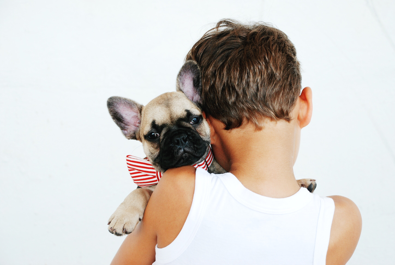 Niño sujetando a perro en brazos